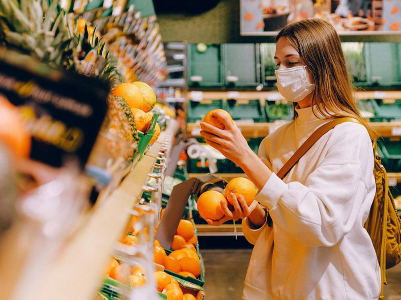 Women wearing a mask is examining oranges in a grocer store