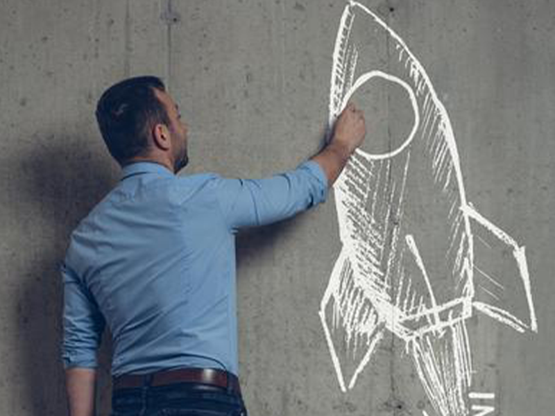 Man drawing a rocket in chalk on a concrete wall